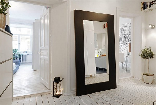 Large glass mirror with brown frame leaning against the for Large glass walls