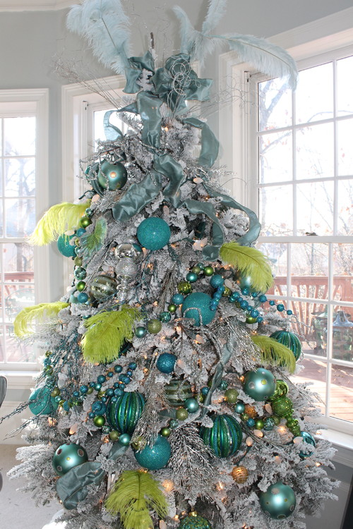 there is nothing traditional about this tree adorned in bright blue and lime green oversized decorations and feathers from unexpected interiors